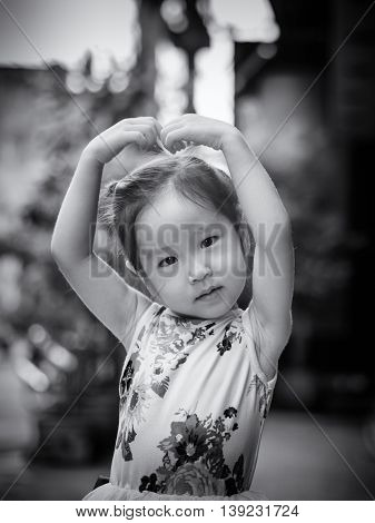 Portrait of a little Asian kid girl with arms like heart action