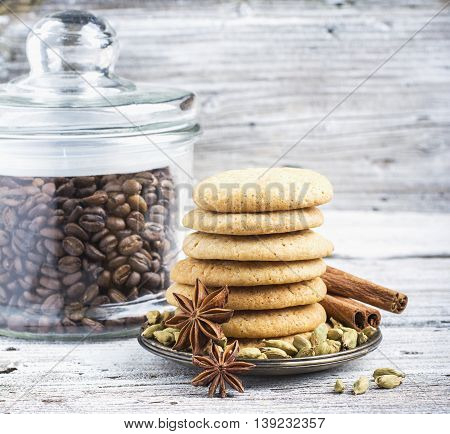 Homemade Danish pastry coolies flavored with cardamom and cinnamon stacked pile surrounded by spices and a jar of coffee beans in the background. Still life on a light wooden rustic background. selective focus