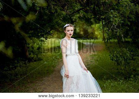 Beautiful girl walking in a white dress in a flowing dress. Dynamics. Boho style in full growth
