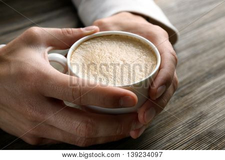 Man holding in hands cup of coffee on wooden background