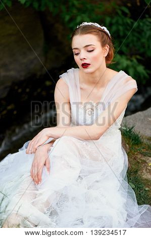 Girl in a beautiful white lace dress straightens her dress. Ballerina. Boho style