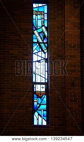 ROMEOVILLE, ILLINOIS / UNITED STATES - MAY 21, 2016: Sunlight shines through a stained glass window in the Saint Charles Borromeo Convocation Hall of Lewis University.