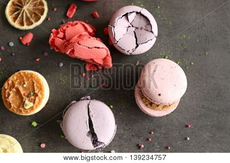 Different colorful macaroons and dry orange slices on gray background