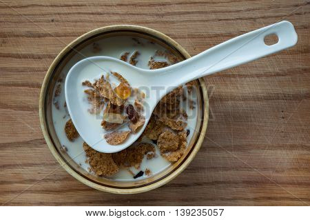 Quick breakfast - cereal with fruit and milk in a bowl and a large spoon.