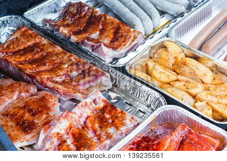 Different kinds of meat and grilled sausage on barbecue grill for great barbecue.