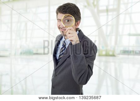Isolated young business man with magnifying glass, at the office