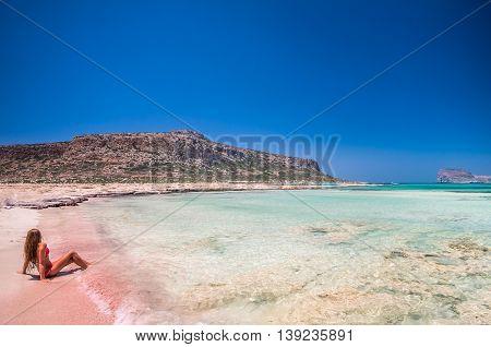 Balos lagoon on Crete island, Greece. A girl on a beach with pink sand.