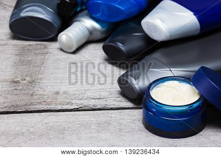 Men's cosmetics background. Various face and body care cosmetic products for men laid out as semicircular frame on old wooden planks. Copy space