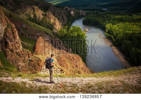 Small figure of a tourist with a backpack and mountain panorama