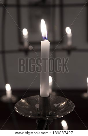 black with white burning candle in a church