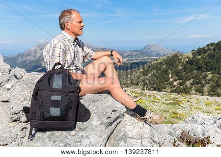 dutch man sitting with backpack in mountain landscape on sunny day