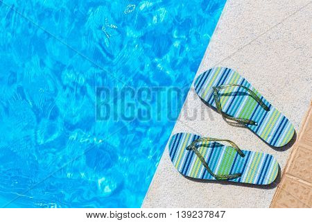 Pair of bathing slippers on edge of blue swimming pool