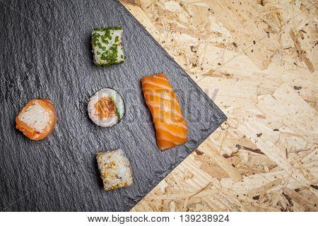 Sashimi and sushi rolls on stone slate