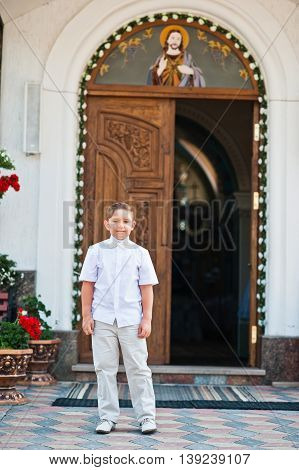 Portrait Of Little Boy On White Wear And Bow Tie On First Holy Communion Background Church Gate
