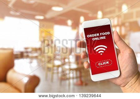Woman hand holding smartphone against blur bokeh of coffee shop background with word order food online