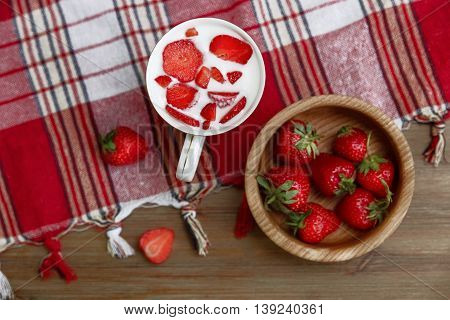 Ceramic Cup of YoghurtRed Fresh Strawberries are in the Wooden Plate on the Check Tablecloth with Fringe.Breakfast Organic Healthy Food.Cooking Vitamins Ingredients.Summer Fruits.Top View