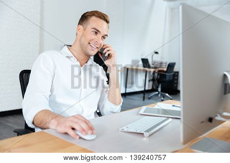 Smiling young businessman working with computer and talking on cell phone at workplace