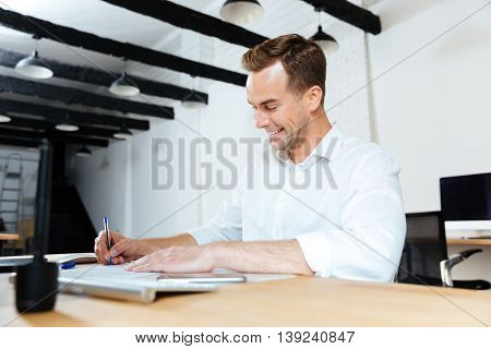 Happy young businessman smiling and writing at the table