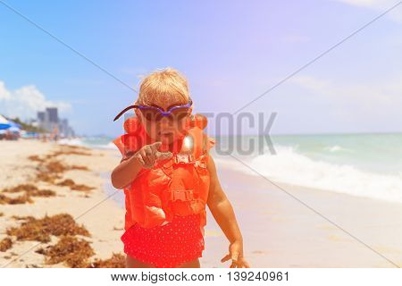 cute little girl in life jacket pointing finger at viewer, safety concept