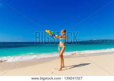 Young beautiful girl in blue bikini having fun on a tropical beach with toy water guns. Blue sea and sky in the background. Summer vacation concept.