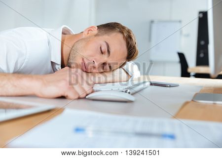 Exhausted fatigued young businessman sleeping on the table in office