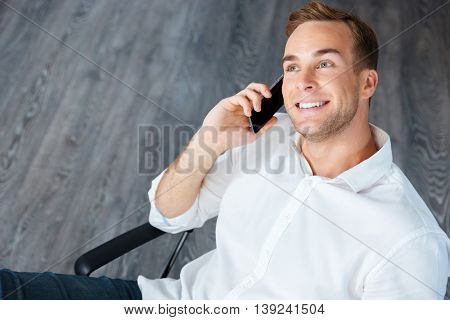 Smiling young businessman sitting and talking on mobile phone in office