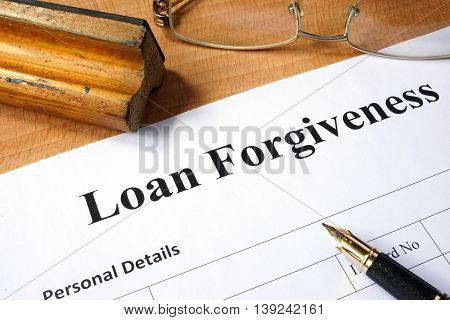 Loan forgiveness form on a wooden table.