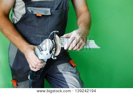 industrial tool, hand grinder cutting plastic. angle grinders in the hands of the builder