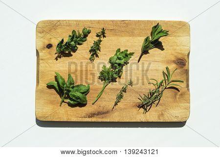 Fresh herbs on wooden cutting board. Flat lay food background.