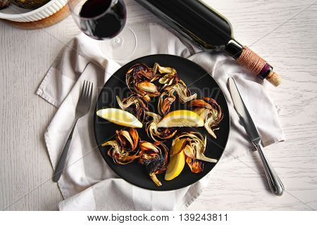 Baked artichokes served with wine on wooden background