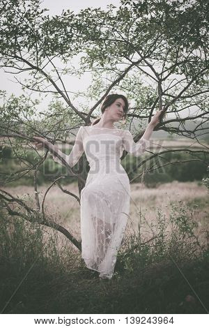 young woman in long lacy dress lean on tree summer day