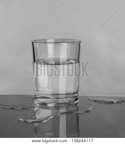Glass and spilled water on grey background