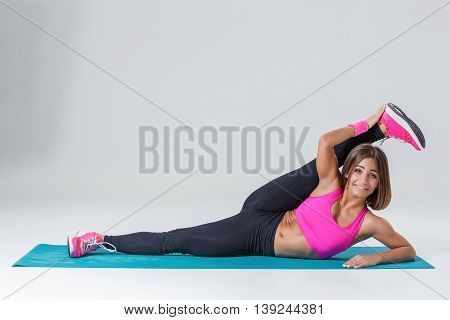 Sport and active lifestyle. Sporty flexible girl fitness woman in pink sportswear doing stretching exercise on light background.