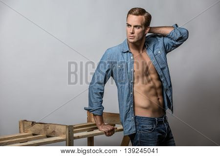 Attractive guy in blue denim unbuttoned shirt and blue jeans stands in the studio on the gray background. His right hand is on a wooden construction, left hand is on the head from behind. Horizontal.