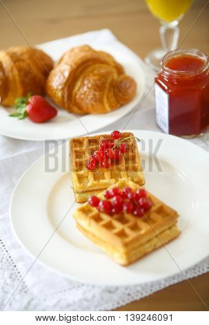 Waffles with red currant jam and berries on a white plate croissants orange juice on the wooden background