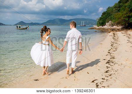 Caucasian prime adult male groom and female bride walking barefoot on beach.