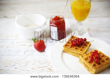 Waffles with red currant jam and berries on a white plate orange juice and oat flakes oatmeal on the wooden background