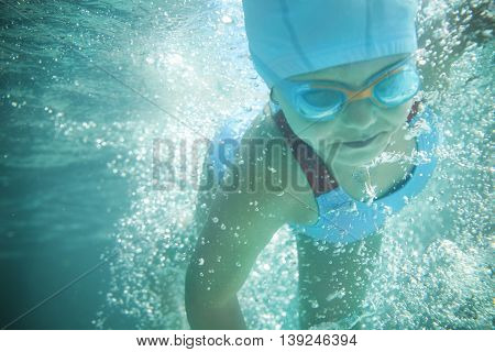 Little girl in a bathing suit swims in the pool underwater