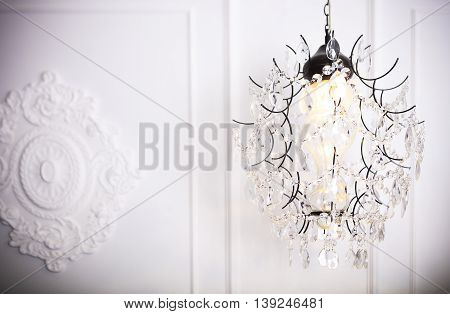 White glass chandelier on white background n classical interior. Glamour background with copy space