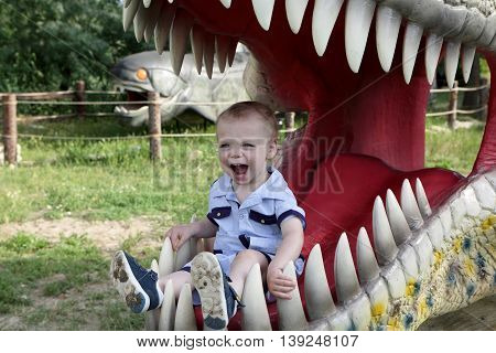 Portrait of boy in jaws of dinosaur