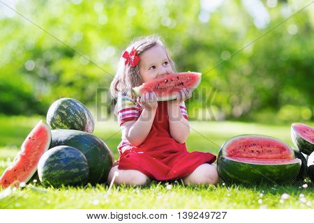 Child eating watermelon in the garden. Kids eat fruit outdoors. Healthy snack for children. Little girl playing in the garden biting a slice of water melon.