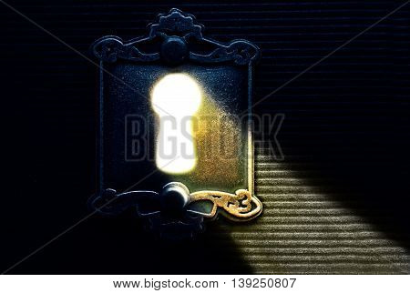 Bright keyhole light shining through old lock