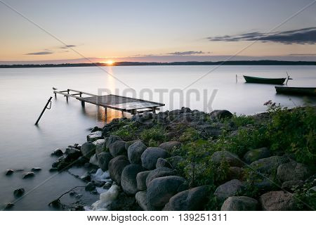 Sun rises over empty footbridge and moored boats. Lasmiady lake Masuria Poland. Long exposure.