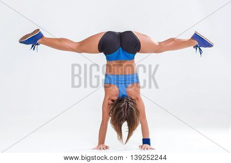 Sport and active lifestyle. Sporty flexible girl fitness woman in blue sportswear doing stretching exercise on light background.