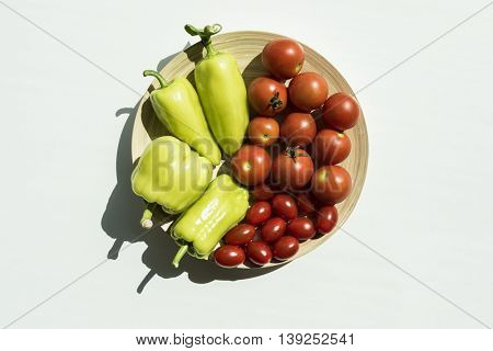 Fresh peppers and tomatoes from garden. Top view on vegetables in bowl lying on white wooden table.