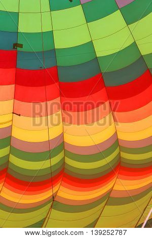 close up of the different colors of a hot air balloon being inflated or deflated