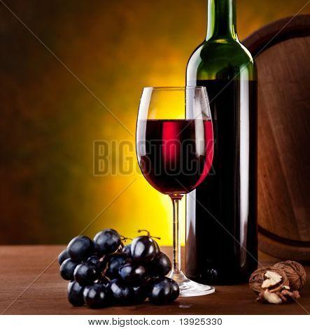 Still life with wine bottle, glass and oak barrels.