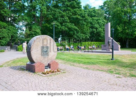 LAPPEENRANTA, FINLAND - JUNE 15, 2016: People sit on the benches near Memorial to orphans of wars next to The Central Park. Foreground is Fourth Infantry Regiment Monument