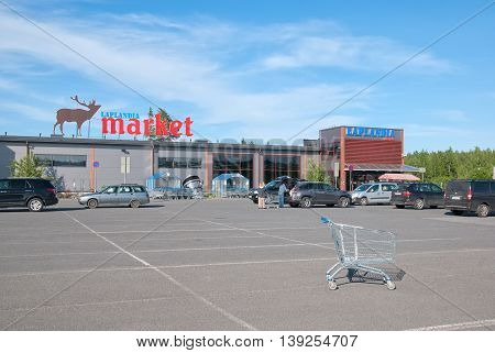 LAPPEENRANTA, FINLAND - JUNE 15, 2016: Laplandia Market near Finnish-Russian border. People put purchases into the car.
