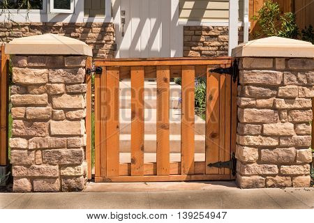 Enclosed Wooden Gate Straight Shape Hinges And Two Stone Posts